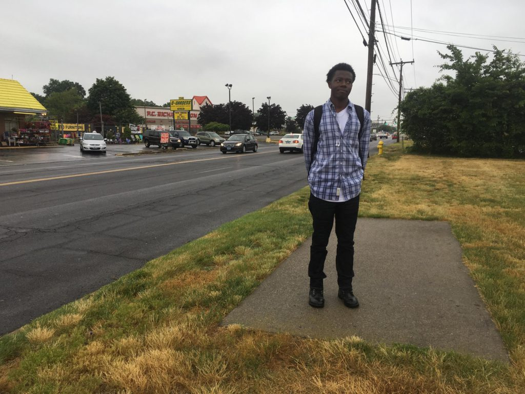 Jaelin McKenzie takes a bus from his home in Bridgeport to a mall in Milford, then walks about a mile on Route 1 to reach the Jos A. Bank clothing store where he works. Here, he's standing on a particularly confusing patch of sidewalk on Route 1. (Cassandra Basler/WSHU)
