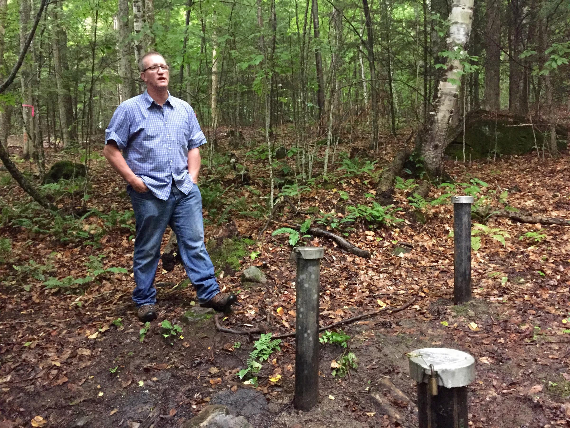Hanover resident Richard Higgins stands near a well 375 feet away from his property, where groundwater tests have shown hundreds of times the New Hampshire state-alloted amount of the chemical 1,4-dioxane, a suspected carcinogen. REBECCA SANANES / VPR