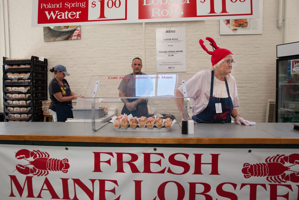 A woman selling lobster rolls in the Maine building says Maine lobster rolls are better than the Connecticut kind. Host John Dankosky disagrees. (Credit: Ryan King/WNPR)