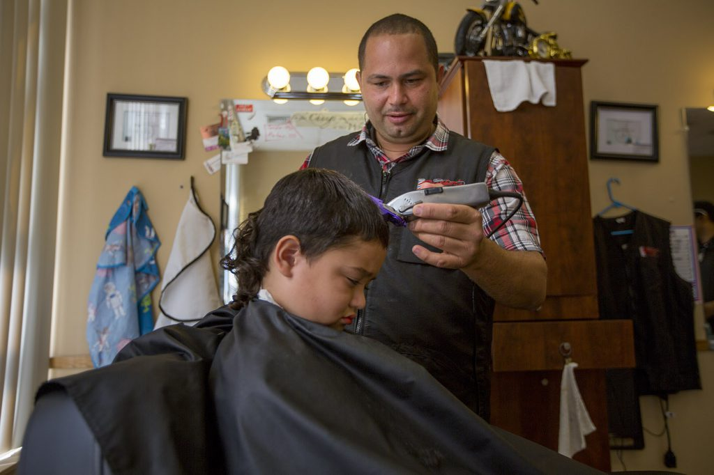 Luis Feliciano cuts the hair of a young boy at the newly opened Brothers Barber Shop on Main Street in Fitchburg. (Credit: Jesse Costa/WBUR)