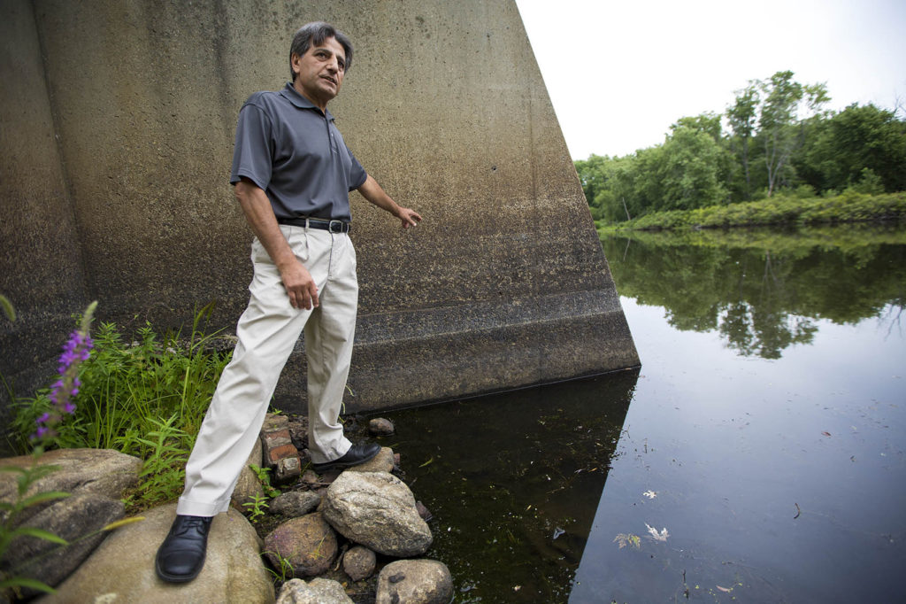 Director of the Billerica Public Works Abdul Alkhatib points out the level of the Concord River is three feet lower than it was this time last year in 2015 due to the current drought condtions this summer. (Jesse Costa/WBUR)