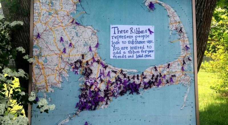 A map of Cape Cod with ribbons representing those lost to substance abuse at the AIDS Support Group of Cape Cod. (Credit: Ryan Sweikert)