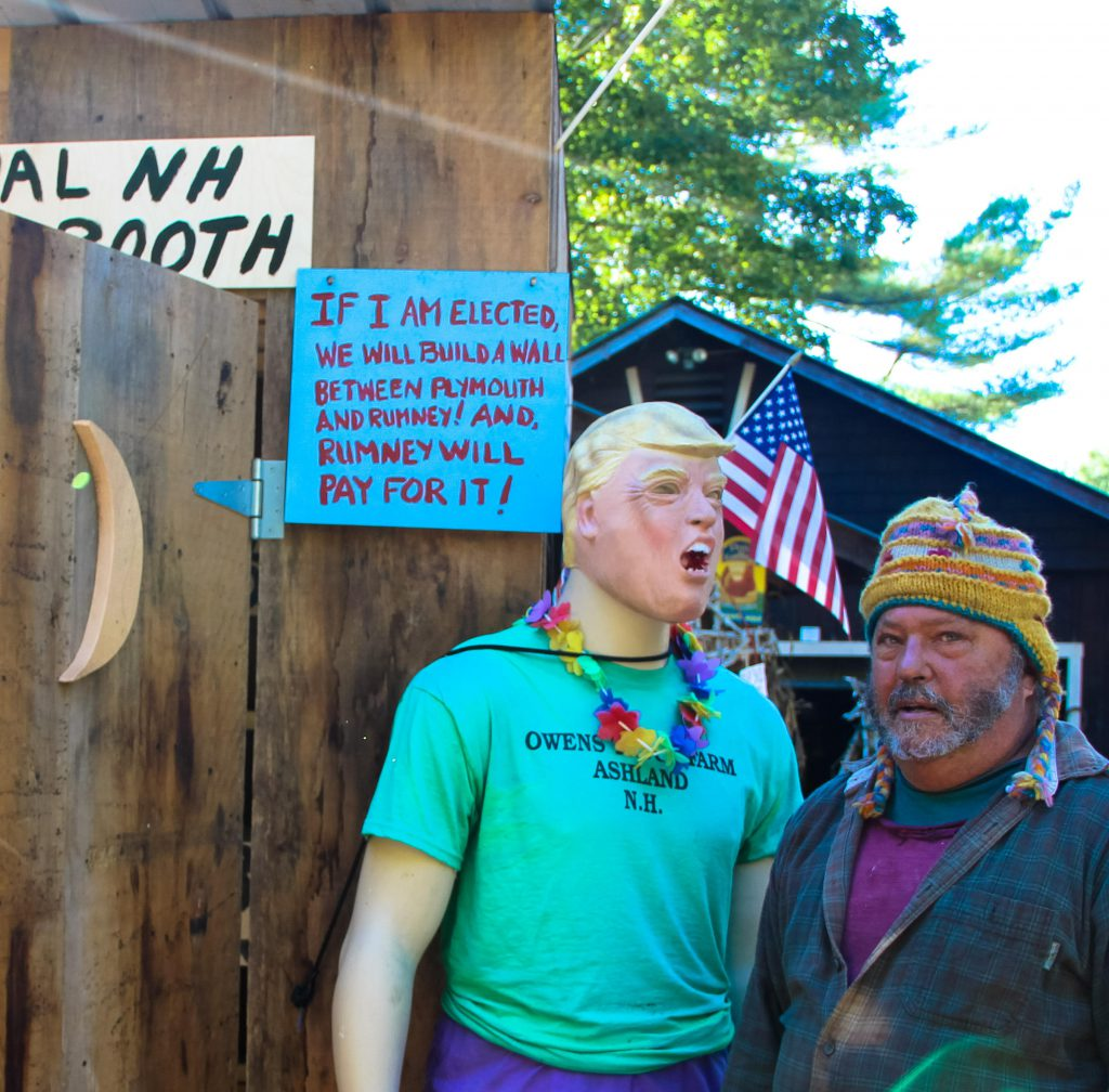 Chris Owens poses with a Donald Trump mannequin outside of his outhouse.