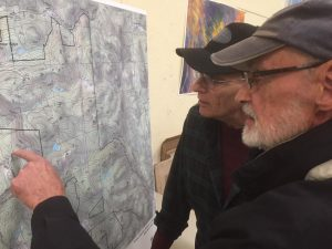 Residents of Windham, Vermont look over a map of the new layout for a proposed wind development. (Credit: Howard Weiss-Tissman/ VPR)