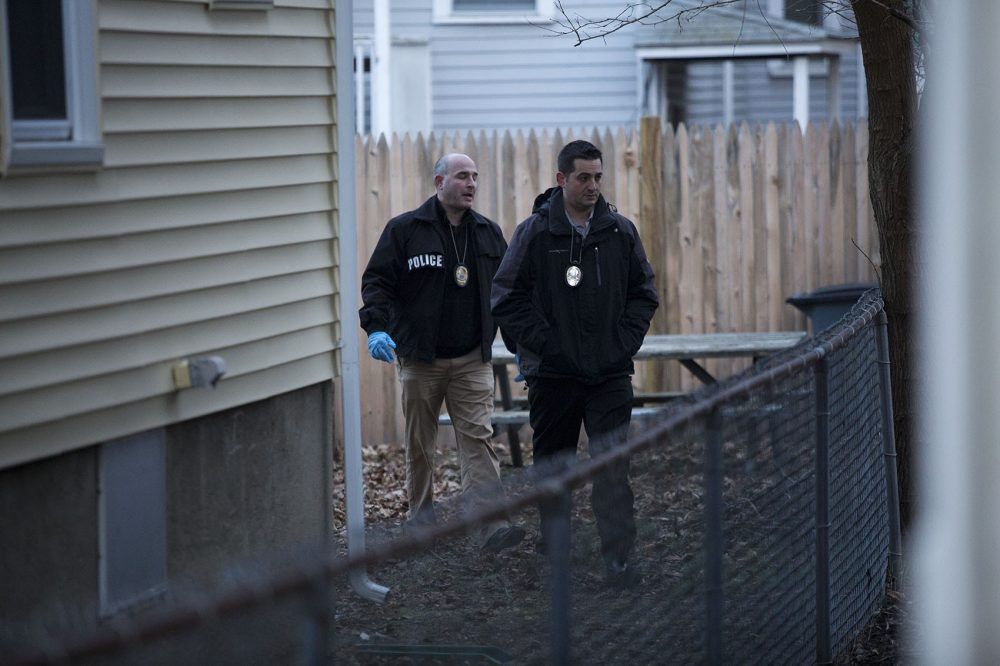 Somerville detectives examine the area where fugitive James Morales was captured, in the backyard of 85 Wheatland St. Photo by Jesse Costa for WBUR.