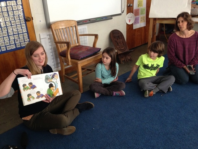"""AmeriCorps VISTA volunteer Alexandra Roche reads from the book """"I'm New Here"""" to third graders at Leeds Elementary School in Northampton, MA. Photo by Nancy Eve Cohen for NEPR."""