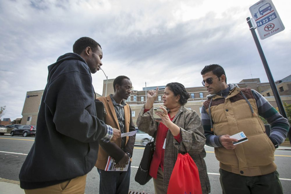 Ascentria Care Alliance, a resettlement agency based in Worcester, announced Monday that as a result of Trump's travel ban it had laid off or reduced hours for 14 employees. In this 2015 photo, an Ascentria instructor shows clients when the next WRTA bus will arrive using a smartphone app. Photo by Jesse Costa for WBUR