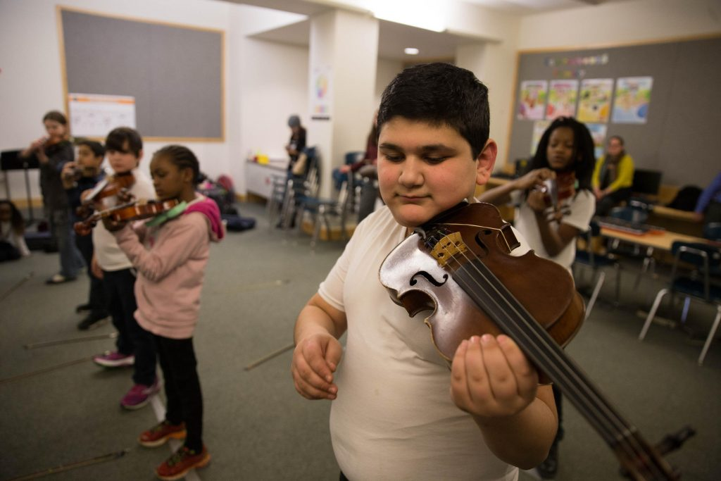 Ahmad Alzouabi plays his violin during class. His family recently arrived in New Haven. Photo by Ryan Caron King for WNPR