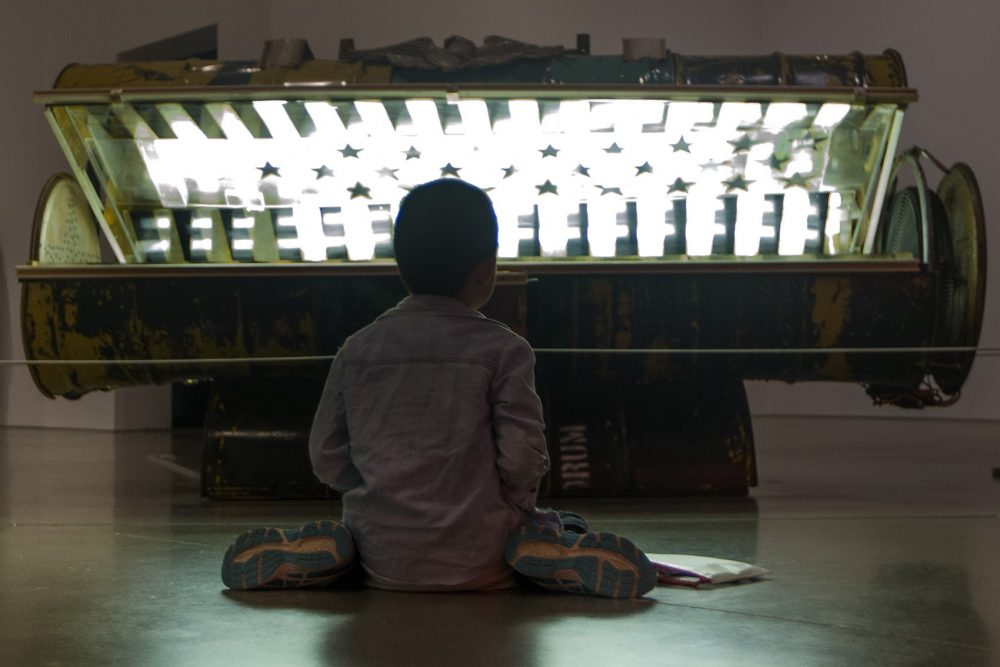 """Nine-year-old Danny Zheng colors on the floor in front of Nari Ward's """"Tanning Bed."""" Photo by Jesse for WBUR."""