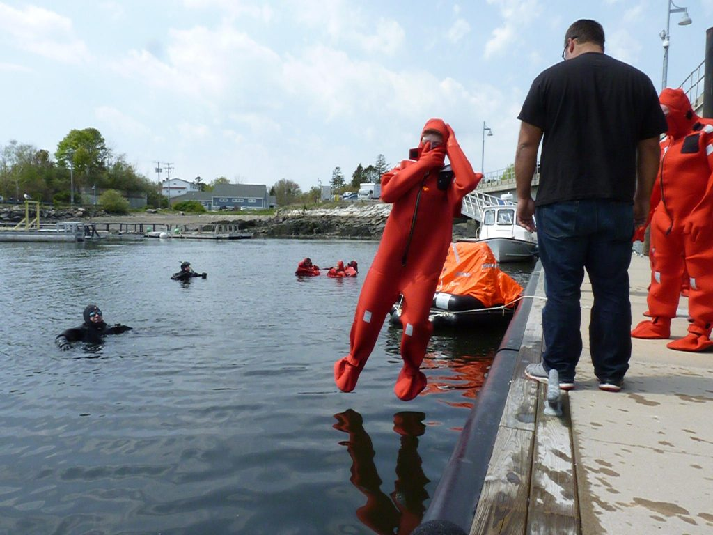 During a day-long safety training seminar in New Castle, commercial fishermen get experience in immersion suits. Photo by Todd Bookman for NHPR