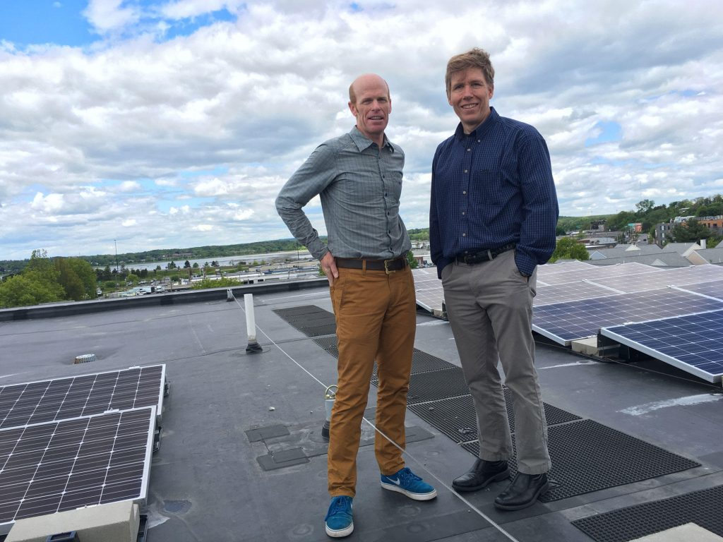 Jesse Thompson of Kaplan Thomas Architects and the Portland Housing Authority's Jay Waterman on top of ultra-efficient Bayside Anchor apartments in Portland, Maine. Photo  by Fred Bever for Maine Public