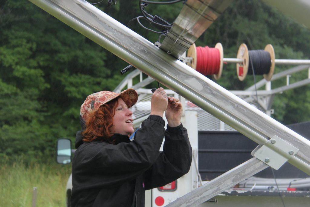 Catamount Solar is installing an 8.7 kilowatt system in a homeowner's yard in East Montpelier. Kestrel Marcel of Catamount Solar is connecting the optimizers, which are a converter technology that helps maximize the energy harvested from the panels. Photo by Kathleen Masterson for VPR