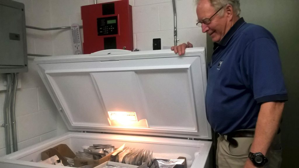 "New England Wildflower Society's Bill Brumback, opening the freezer that acts as the ""seed vault,"" in Framingham, Mass. Photo by Jill Kaufman for NEPR"