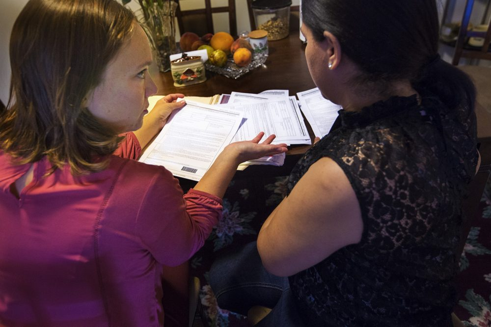 Some immigrants living here without authorization who've been victims of crime in the U.S. may be eligible for a U visa. The application process and lengthy wait time used to be a deterrent, but that appears to be changing under the Trump administration. Here, immigration lawyer Susan Roses, left, reviews documents and with Antonia concerning her U-visa filing. Photo by Jesse Costa for WBUR