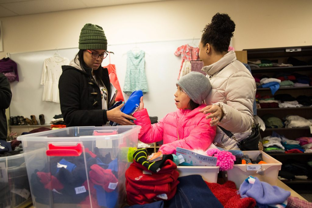 In the hurricane relief center in Hartford, Kaliel Diaz (center) goes through winter clothing with her mom Nydia Marcano (left) and her cousin Marlene Hernandez (right). Photo by Ryan Caron King for WNPR
