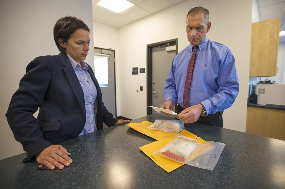"Arlington Police Chief Fred Ryan, right, and inspector Gina Bassett review toxicology reports on cocaine evidence, looking for the possibility of fentanyl. ""Law enforcement tells us that the next wave of the addiction crisis is fentanyl-laced cocaine,"" Ryan says. Photo by Jesse Costa for WBUR"