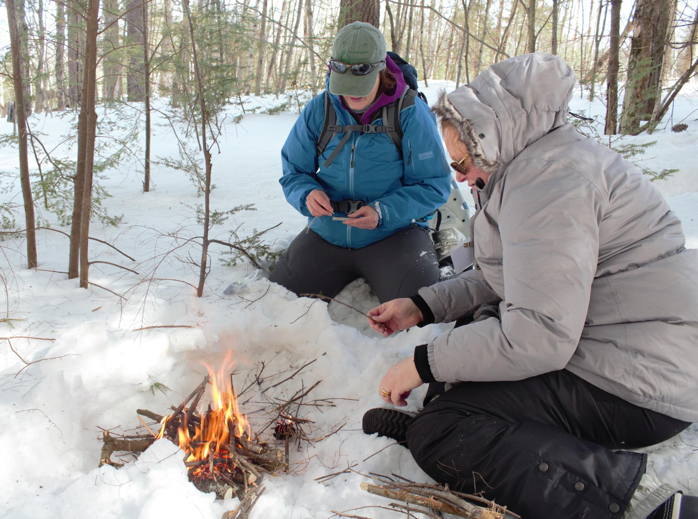 Julia Wilcox and Claire Rouge tend to a fire they made during BOW's winter survival skills class. Photo by Annie Ropeik for NHPR