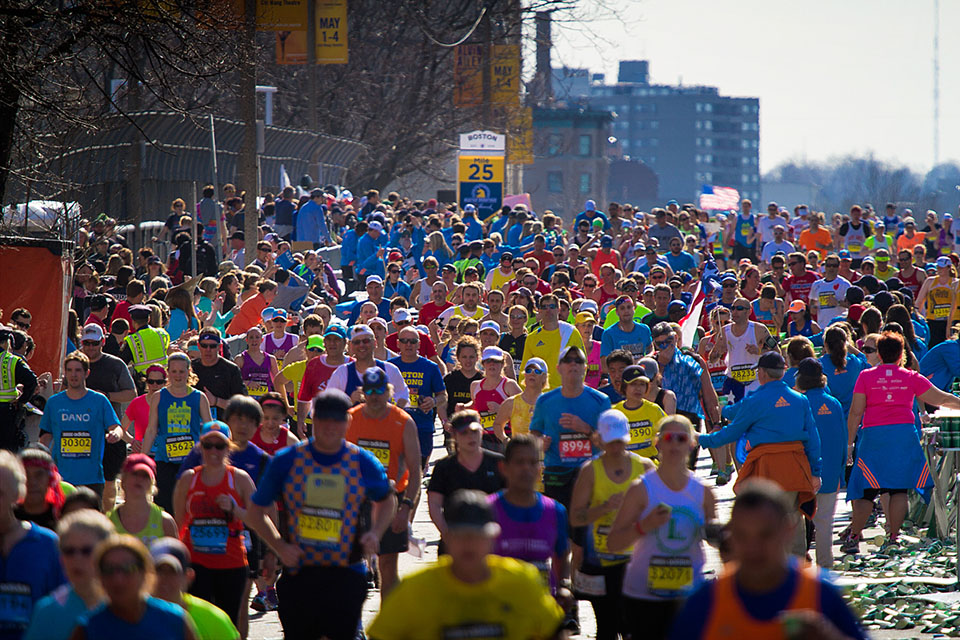 Runners pour over the Mass Pike overpass at mile 25 in the 2014 Boston Marathon. Photo by Jesse Costa for WBUR