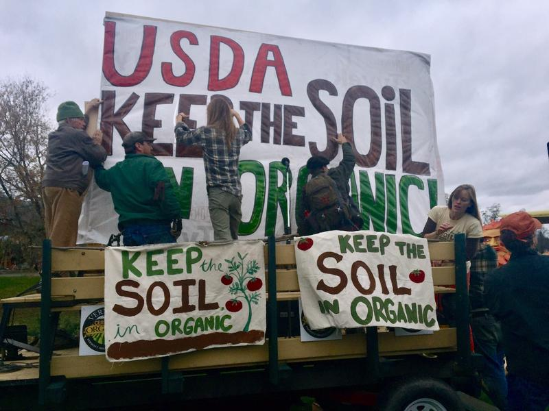 "A rally in Thetford back in 2016 criticized the USDA's move to allow vegetables raised hydroponically to be labeled as ""organic."" Now a movement has formed to strengthen the organic label. Photo by Rebecca Sananes for VPR"