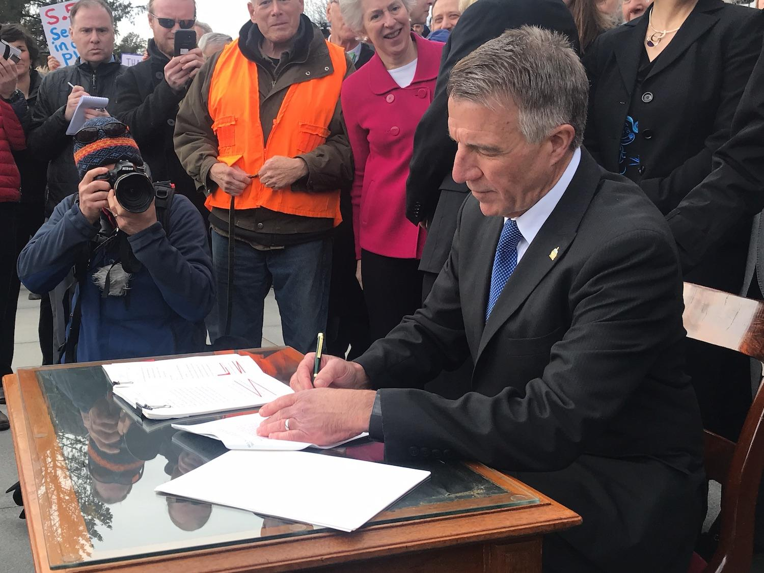 Gov. Phil Scott signs three pieces of gun control legislation amid boos and cheers on the front steps of the statehouse Wednesday, April 11, 2018. Photo by Emily Alfin Johnson for VPR.