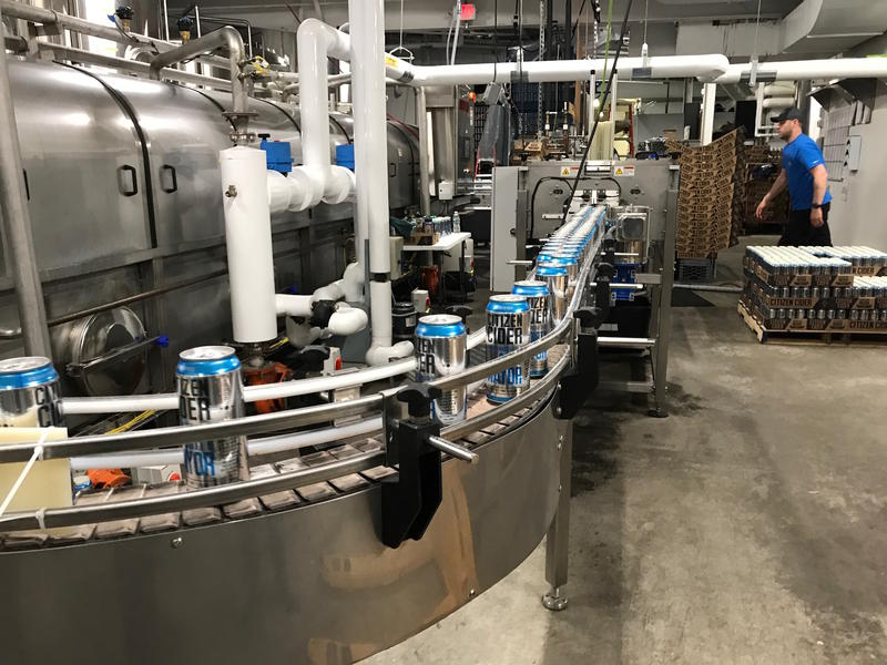 "Aluminum cans of Citizen Cider's ""Dirty Mayor"" make their way on the canning belt at the company's Burlington canning facility. A new tariff on some imported steel and aluminum has Vermont craft brewers and cider makers bracing for uncertainty."
