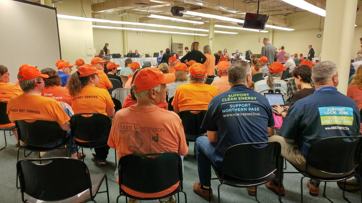 Orange-shirted opponents of Northern Pass sit with blue-shirted supporters at the Site Evaluation Committee Thursday. Photo by Annie Ropeik for NHPR