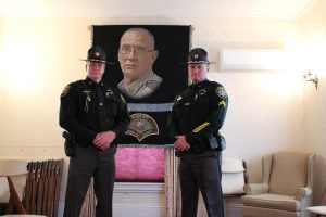 Two officers from the Sagadahoc County Police Department, watching over the casket of Eugene Cole at the Smart and Edwards Funeral Home in Skowhegan. Photo by Robbie Feinberg for Maine Public