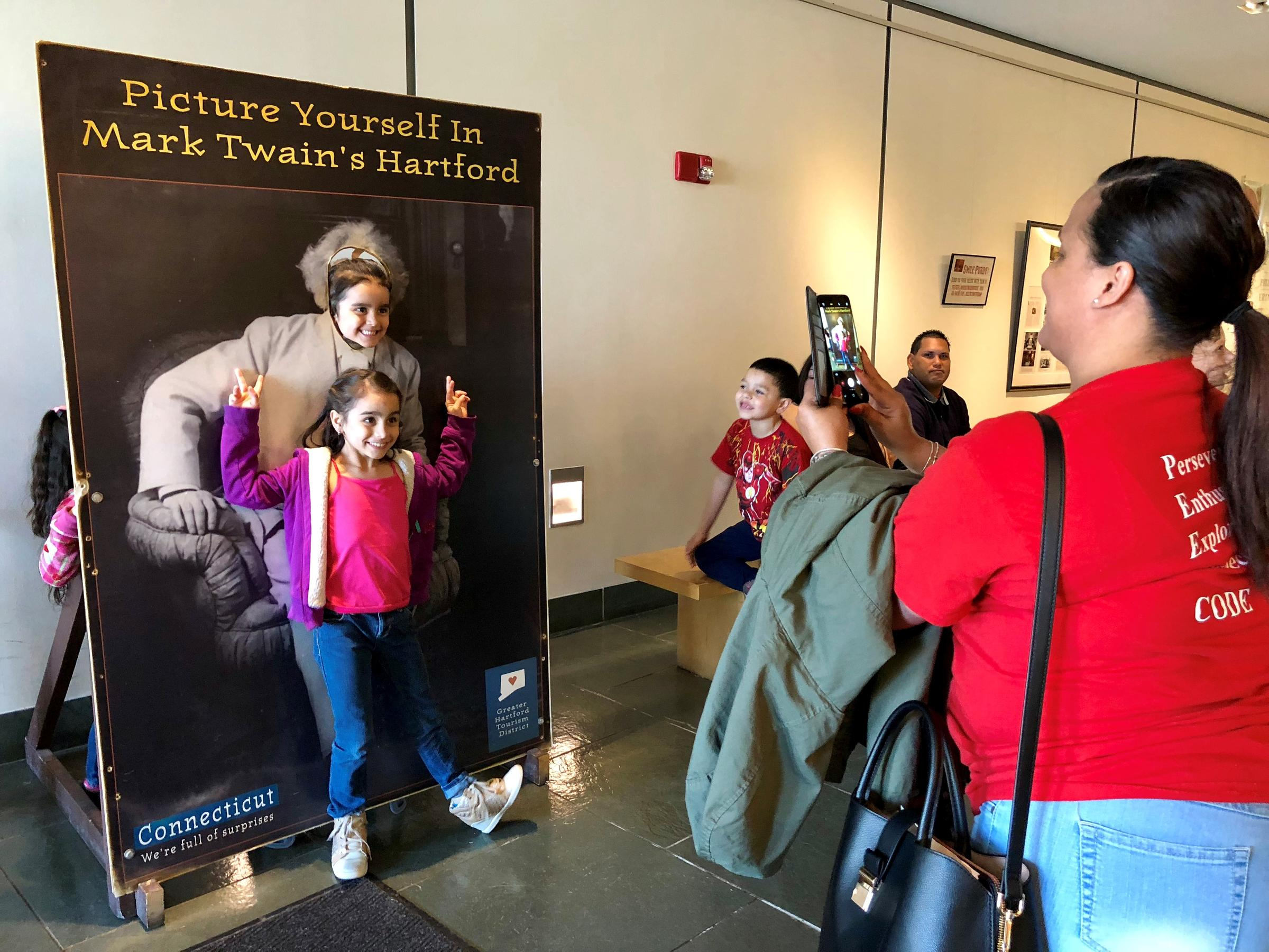 Sanchez School employee Sally Vazquez, right, takes a photo of Hartford students in the lobby of the Mark Twain House & Museum. Families displaced from Puerto Rico were invited to the American landmark. Photo by Vanessa de la Torre for Connecticut Public Radio