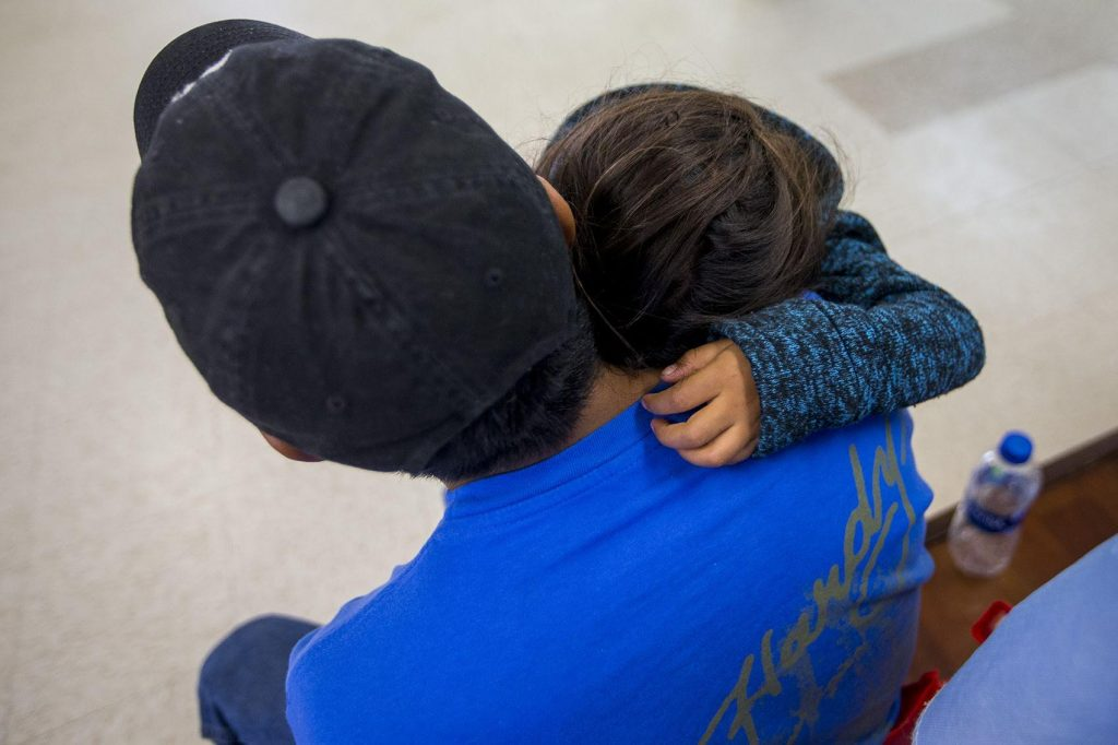 A young migrant family waits for the arrangements for their bus at Catholic Charities in McAllen, TX. Photo by Jesse Costa for WBUR