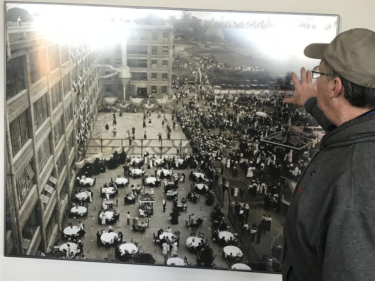 Mike Bernier points to a photo of a factory employee party that took place on the grounds of what is now the Sundial Center. Photo by Robert Garrova for NHPR
