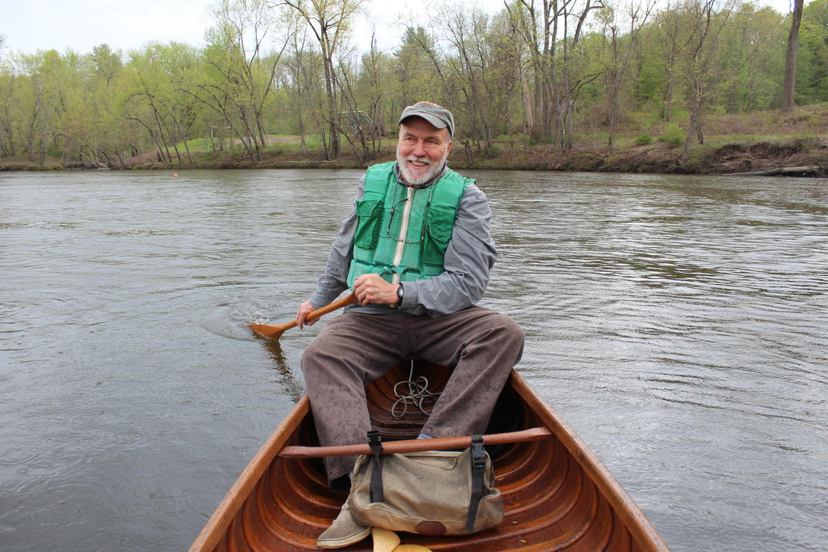 Norm Sims paddles one of his wood and canvas canoes on the Connecticut River. Photo by Annie Ropeik for NHPR