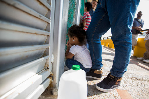 A three-year-old from Honduras peers through a fence at the U.S. - Mexico border while her family waits to apply for asylum. Photo by Jesse Costa for WBUR