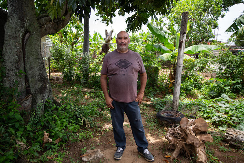 Hurricane Maria destroyed Ramón Luis Morales's roof, but he hasn't been able to finish rebuilding because he's still waiting on supplies. In the meantime, he's helping another man in need fix his house. Photo by Ryan Caron King for Connecticut Public Radio
