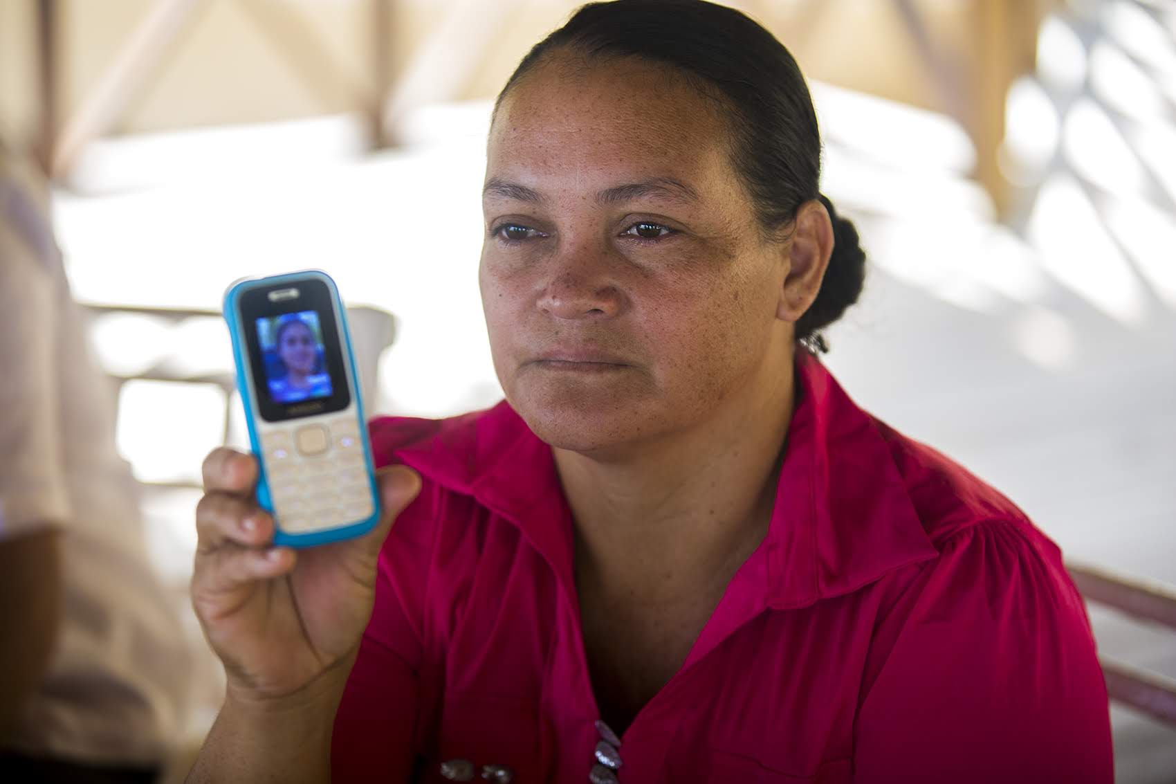Rosa Lina Linder shows a photograph of her 16-year-old daughter on her cellphone, still being detained in the U.S. Photo by Jesse Costa for WBUR