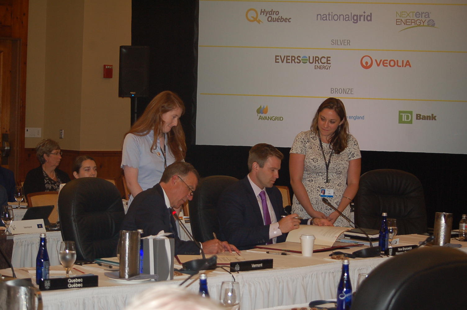Vermont Gov. Phil Scott, left, and New Brunswick Premier Brian Gallant sign resolutions at Monday's annual conference of New England governors and eastern Canadian premiers. Gallant will host next year's meeting in St. John, New Brunswick. Photo by John Dillon for VPR