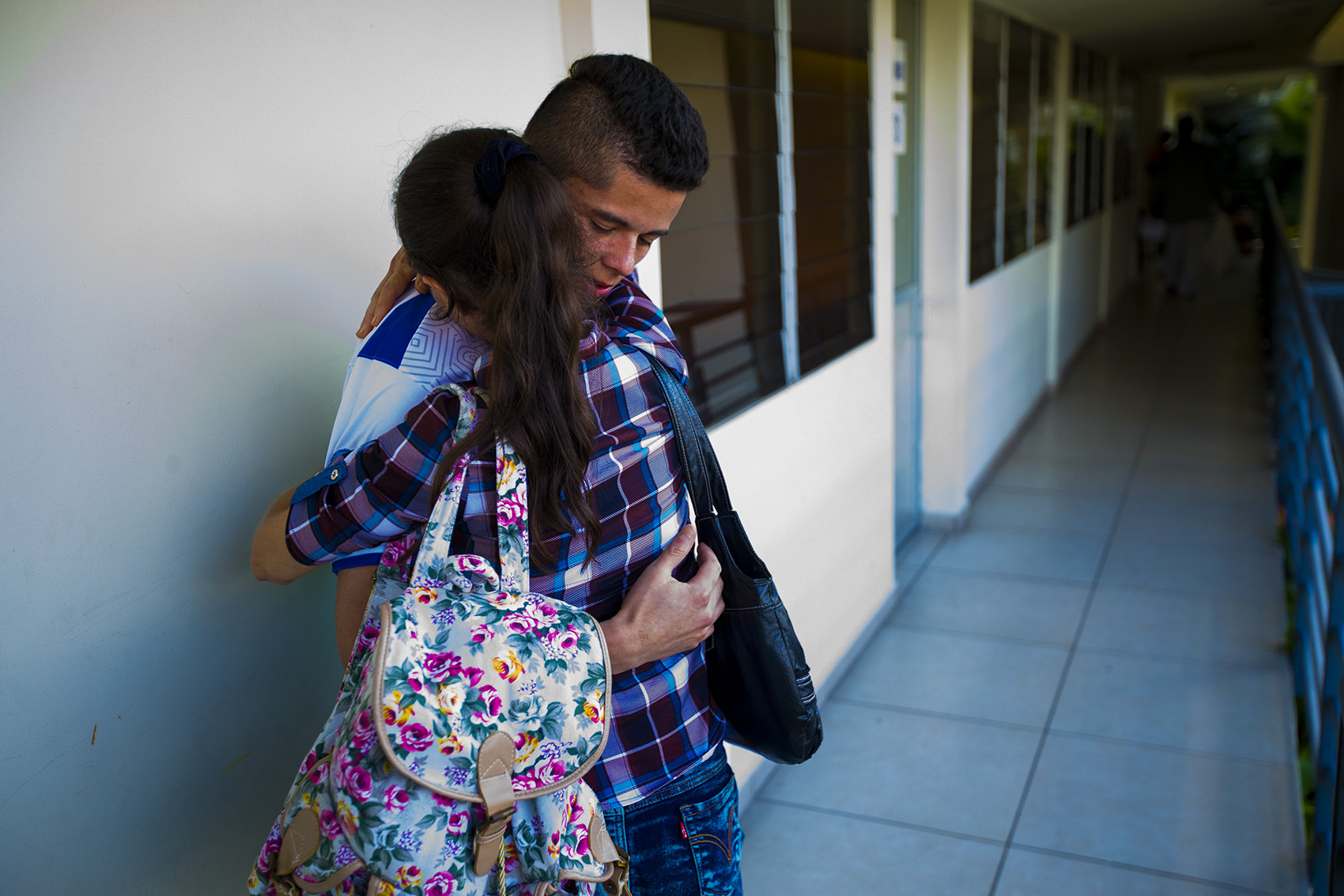 A 21-year-old man deported from Boston is reunited with his mother at the Centro de Atención integral a Migrante (Comprehensive Migrant Care Center) in San Salvador. Photo by Jesse Costa for WBUR