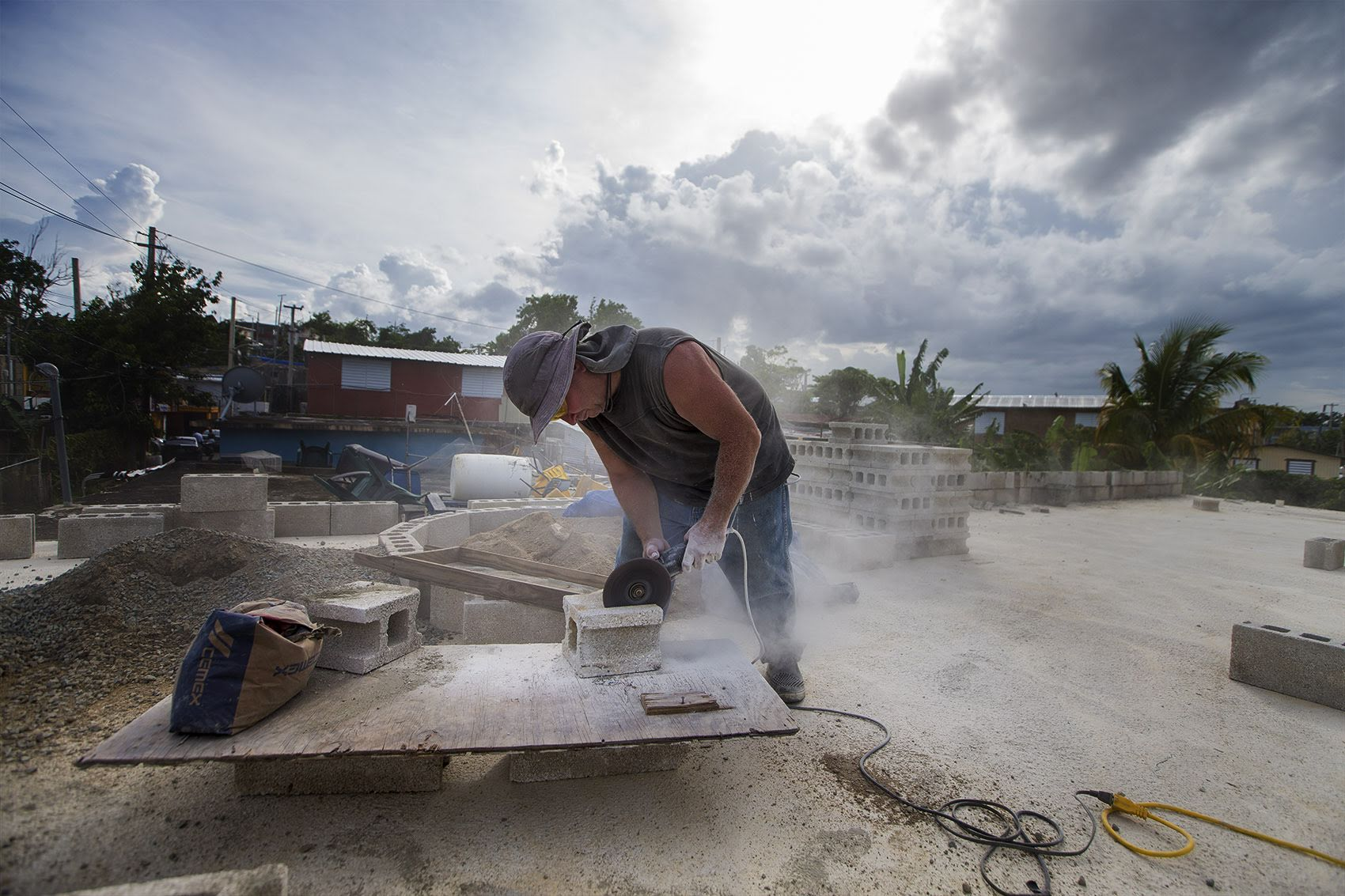Jose Contreras saws a concrete block in half as he rebuilds his house in Barrio-Bravos de Boston, San Juan, which was completely destroyed by Hurricane Maria a year ago . Photo by Jesse Costa for WBUR