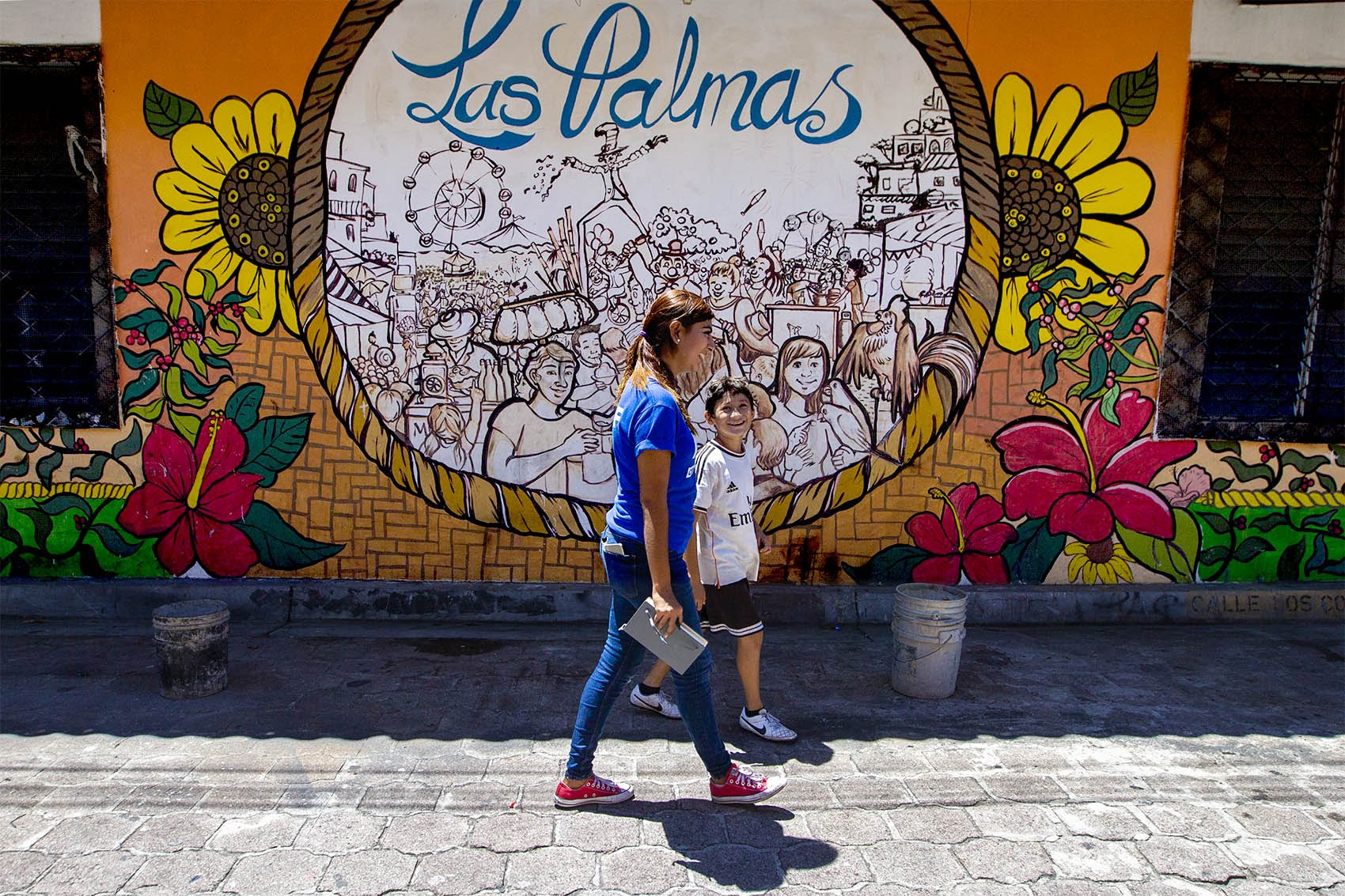 A Glasswing International staff member walks through town with a young boy who lives in Las Palmas. Photo by Jesse Costa for WBUR