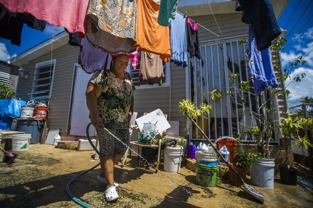 Angelina Arroyo sprays her driveway down during a hot afternoon in Punta Santiago. Her husband had a heart attack shortly after the hurricane last year and passed away soon after. Photo by Jesse Costa for WBUR