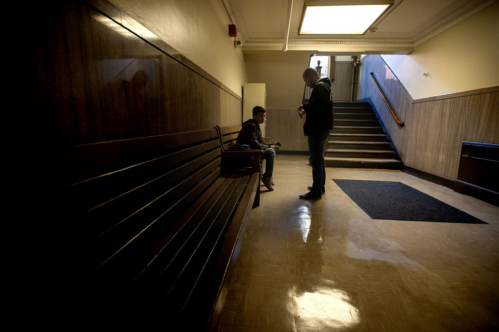 Diego Pizarro, a front line youth worker at Roca, stops to talk with a young man in East Boston District Court. Photo by Jesse Costa for WBUR