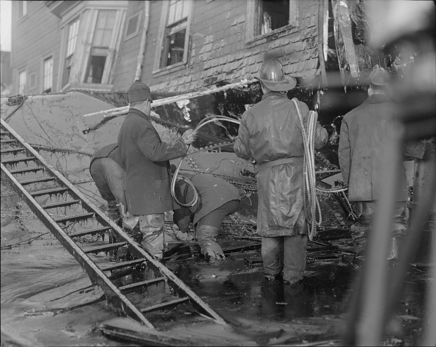 Firemen standing in thick molasses after the disaster. Courtesy of the Boston Public Library, Leslie Jones Collection.