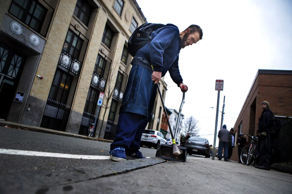 Michael sweeping up cigarettes and other debris from the sidewalk outside the ACC Needle Exchange in Central Square in Cambridge. Photo by Jesse Costa for WBUR
