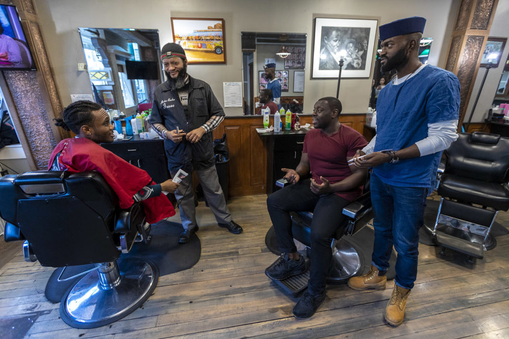 "From right to left: Bright Genty and his father, master barber Isaac, speak with ""Barber Shop Chronicles"" actor Ekow Quartey and the production's writer Inua Ellams at Headlines Unisex Barbershop in Cambridge. Photo by Jesse Costa for WBUR"
