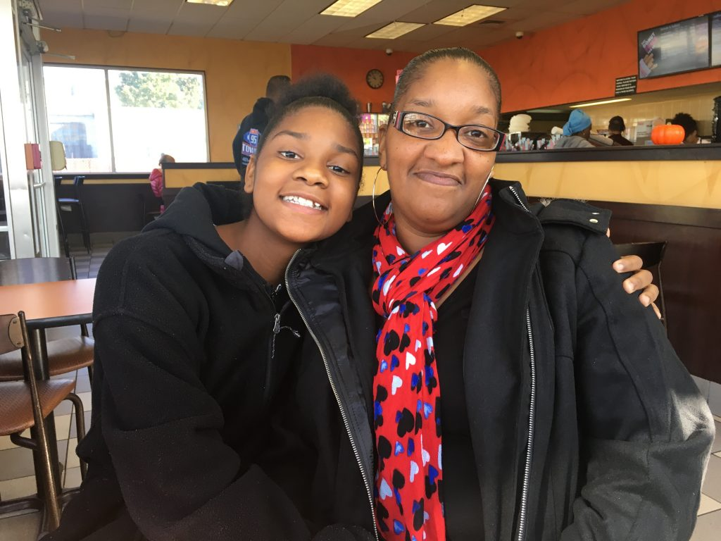 Kennekca Kindell (right) and her 14-year-old daughter, Kanija Kindell, visit the Dunkin' Donuts in Pawtucket where Kennekca works. Photo by Avory Brookins for The Public's Radio