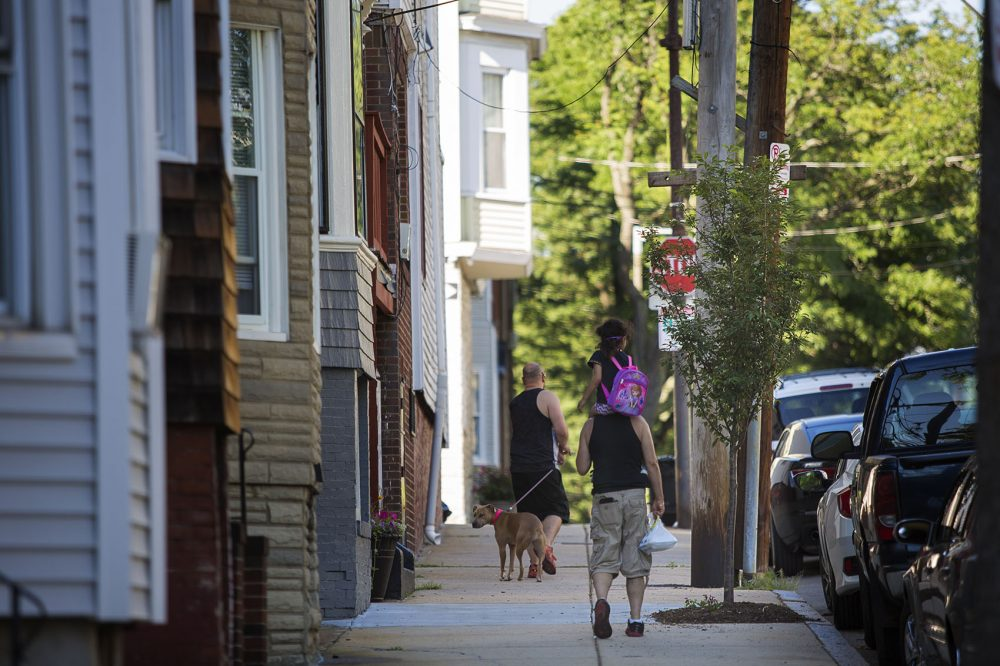 East Boston neighbors walk by a tree recently planted on Trenton Street. Photo by Jesse Costa for WBUR
