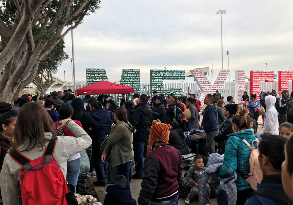 "Families wait at ""El Chaparral,"" a border crossing near San Ysidro, California, to hear which names are called from the asylum waitlist. Photo by Shannon Dooling for WBUR"