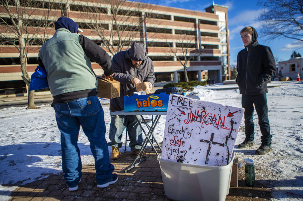 On a frigid 17º F afternoon in Pickering Square in Bangor, ME, two men stop by a folding table set up by The Church of Safe Injection for some coffee. Photo by Jesse Costa for WBUR