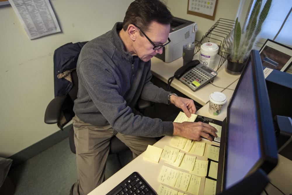 Army veteran Chris Riga rearranges sticky notes on his desk which he uses to organize and to assist him in remembering tasks he has to do throughout the day at his job as patient experience coordinator at the Northampton VA Medical Center in Leeds, MA. Photo by Jesse Costa for WBUR