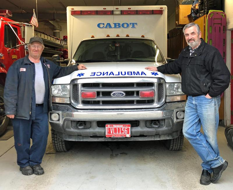EMT Andy Luce, left, and Cabot Select Board Chair Michael Hogan, right, stand with the town ambulance, housed at the Cabot Fire Department. The town's emergency ambulance service will stop transporting patients in June. Photo by Amy Kolb Noyes for VPR