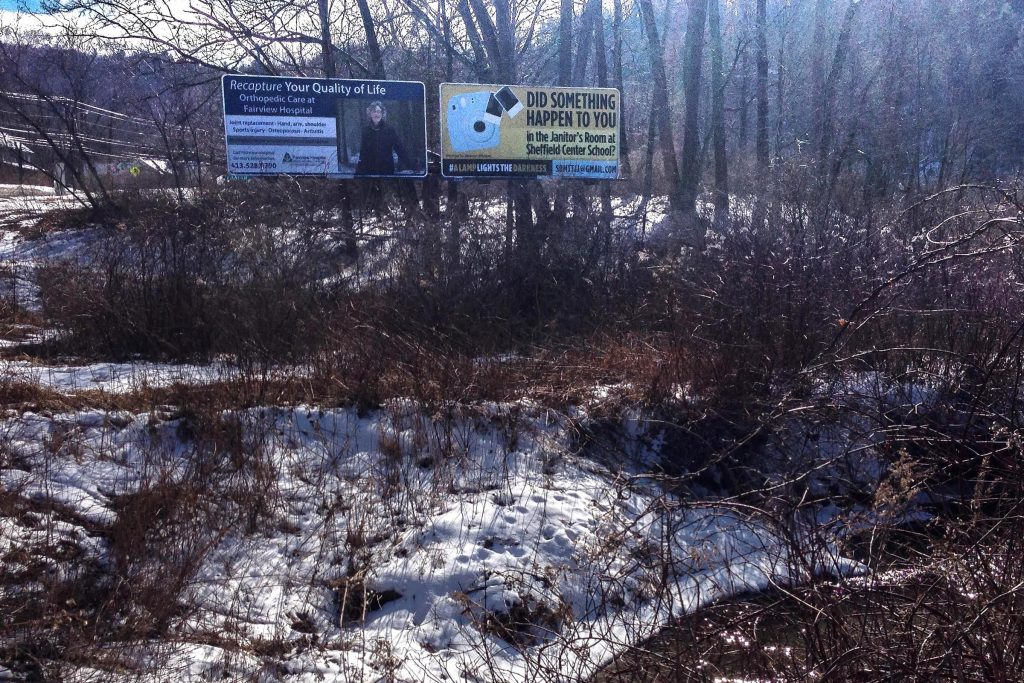 A billboard, at right, on Route 7 in Great Barrington, Massachusetts, was paid for by the mother of a man who says he was sexually abused decades ago in a now-closed elementary school in Sheffield. This one went up in February. Photo by Nancy Eve Cohen for NEPR